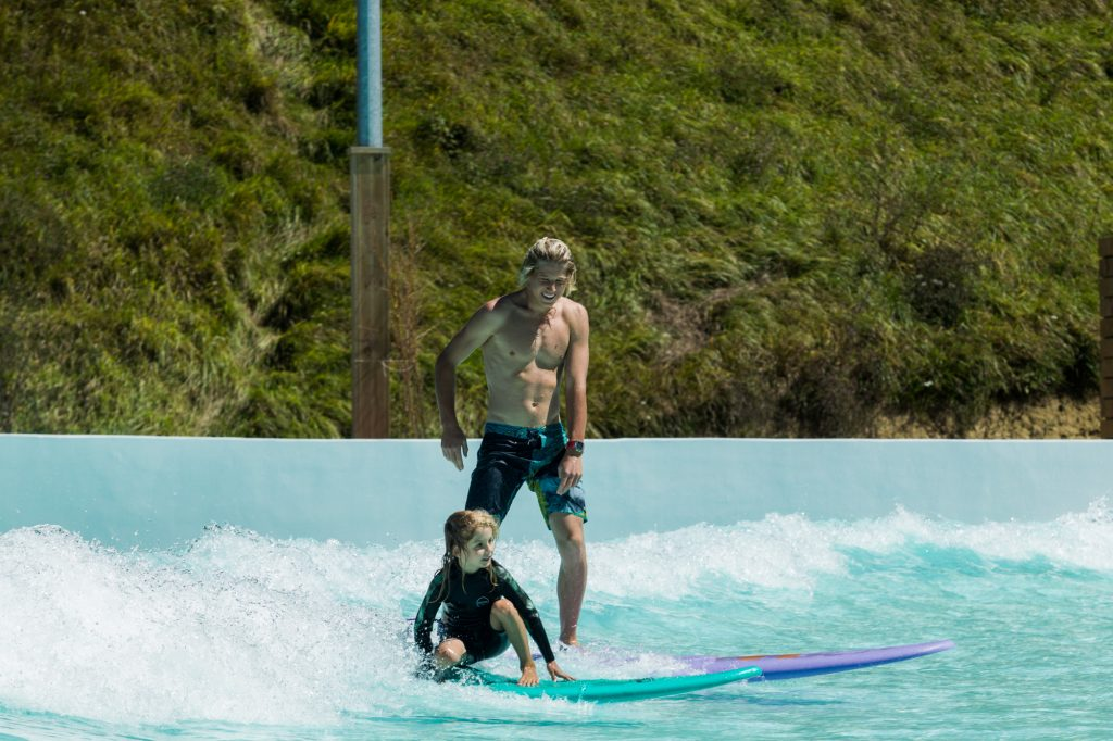 father and son wave pool surfing