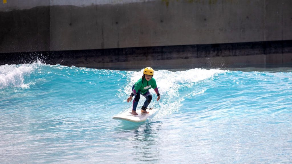 child at an adaptive surfing event in a wave pool